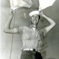 Photo of Signalman 3rd Class James R. Ethridge, Jr. with signal flags