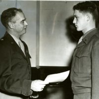 Photo of Pvt. Vernon H. Dalluge receiving commendation from Brig. Gen. Donald F. Fritch